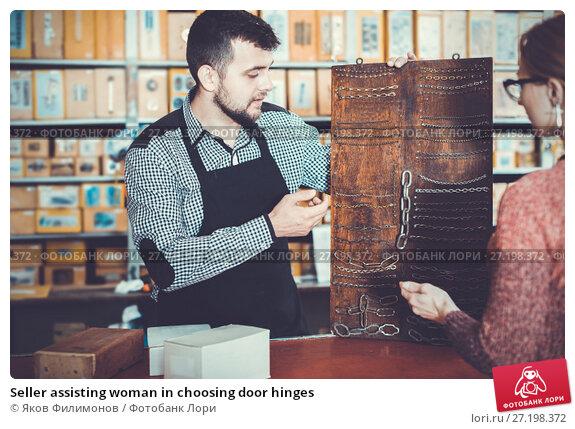 Купить «Seller assisting woman in choosing door hinges», фото № 27198372, снято 5 апреля 2017 г. (c) Яков Филимонов / Фотобанк Лори