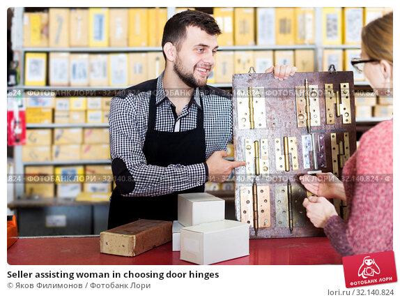 Купить «Seller assisting woman in choosing door hinges», фото № 32140824, снято 5 апреля 2017 г. (c) Яков Филимонов / Фотобанк Лори