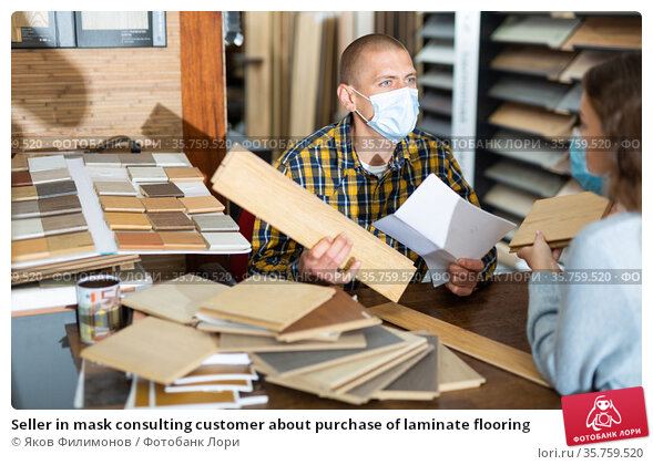 Seller in mask consulting customer about purchase of laminate flooring. Стоковое фото, фотограф Яков Филимонов / Фотобанк Лори