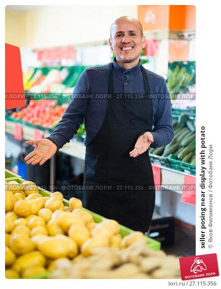 Купить «seller posing near display with potato», фото № 27115356, снято 11 декабря 2018 г. (c) Яков Филимонов / Фотобанк Лори