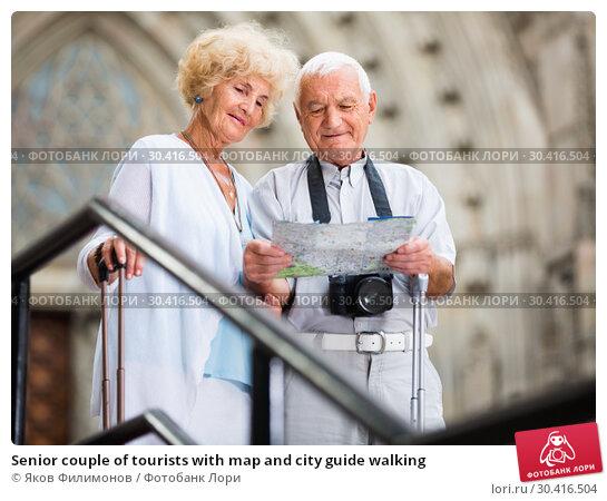 Купить «Senior couple of tourists with map and city guide walking», фото № 30416504, снято 16 сентября 2019 г. (c) Яков Филимонов / Фотобанк Лори
