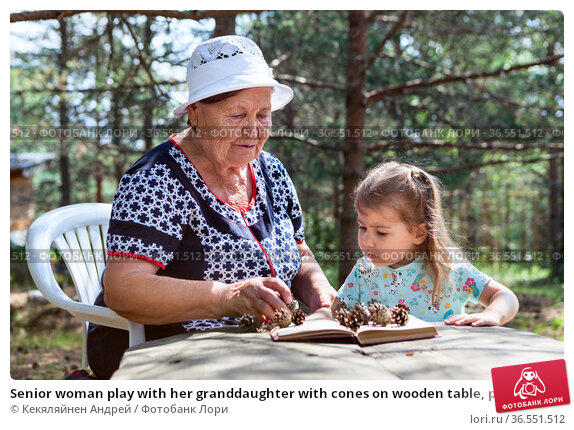 Senior woman play with her granddaughter with cones on wooden table, people living in village. Стоковое фото, фотограф Кекяляйнен Андрей / Фотобанк Лори