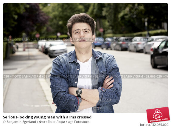 Serious-looking young man with arms crossed. Стоковое фото, фотограф Benjamin Egerland / age Fotostock / Фотобанк Лори