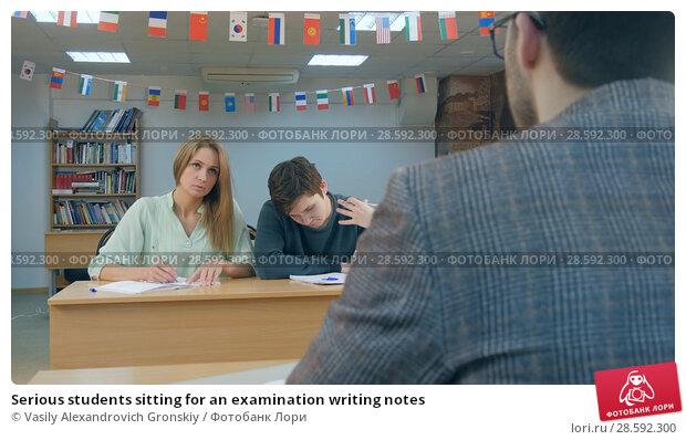 Купить «Serious students sitting for an examination writing notes», фото № 28592300, снято 21 сентября 2018 г. (c) Vasily Alexandrovich Gronskiy / Фотобанк Лори