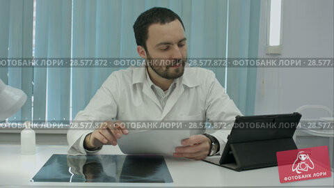 Купить «Serious young bearded doctor uses his digital tablet.», видеоролик № 28577872, снято 24 ноября 2015 г. (c) Vasily Alexandrovich Gronskiy / Фотобанк Лори