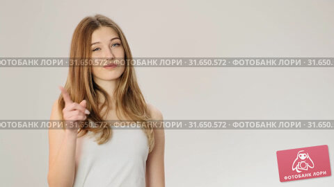 Serious young woman showing denying gesture and looking at camera while standing isolated over gray background slow motion. Стоковое видео, видеограф Denis Mishchenko / Фотобанк Лори