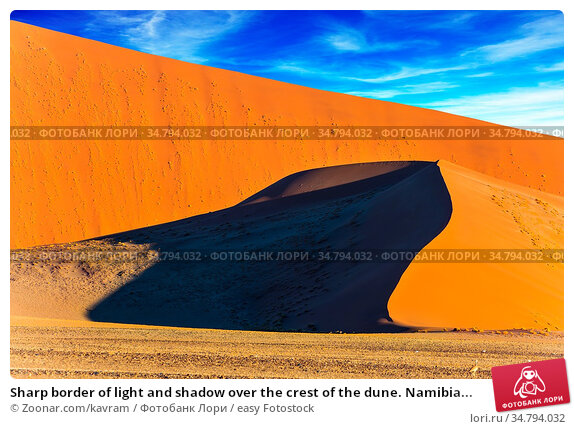 Sharp border of light and shadow over the crest of the dune. Namibia... Стоковое фото, фотограф Zoonar.com/kavram / easy Fotostock / Фотобанк Лори