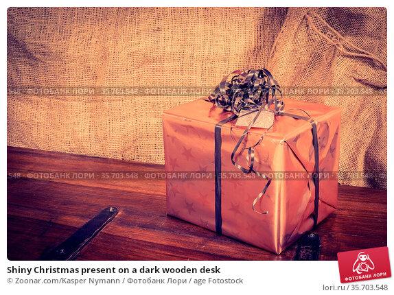 Shiny Christmas present on a dark wooden desk. Стоковое фото, фотограф Zoonar.com/Kasper Nymann / age Fotostock / Фотобанк Лори