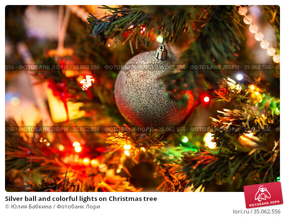 Silver ball and colorful lights on Christmas tree. Стоковое фото, фотограф Юлия Бабкина / Фотобанк Лори