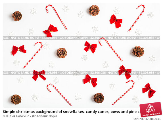 Купить «Simple christmas background of snowflakes, candy canes, bows and pine cones on a white background», фото № 32306036, снято 19 октября 2019 г. (c) Юлия Бабкина / Фотобанк Лори