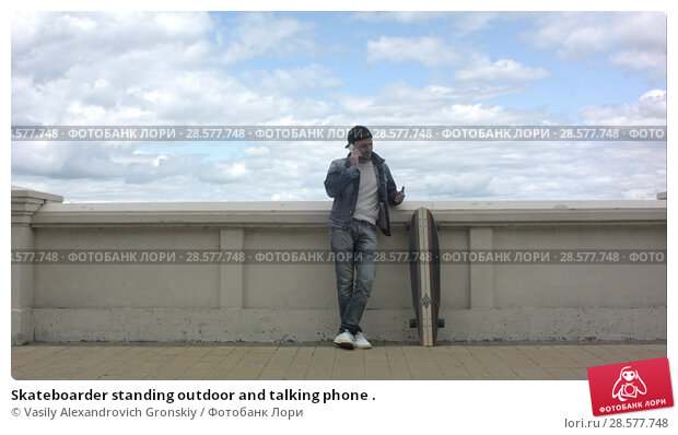 Купить «Skateboarder standing outdoor and talking phone .», фото № 28577748, снято 19 июня 2018 г. (c) Vasily Alexandrovich Gronskiy / Фотобанк Лори