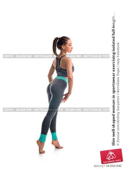 Slim well-shaped woman in sportswear exercising isolated full-length... Стоковое фото, фотограф Zoonar.com/Andrey Guryanov / easy Fotostock / Фотобанк Лори