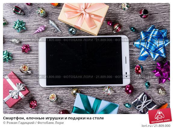 Купить «Смартфон, елочные игрушки и подарки на столе», фото № 21809000, снято 18 ноября 2015 г. (c) Роман Гадицкий / Фотобанк Лори