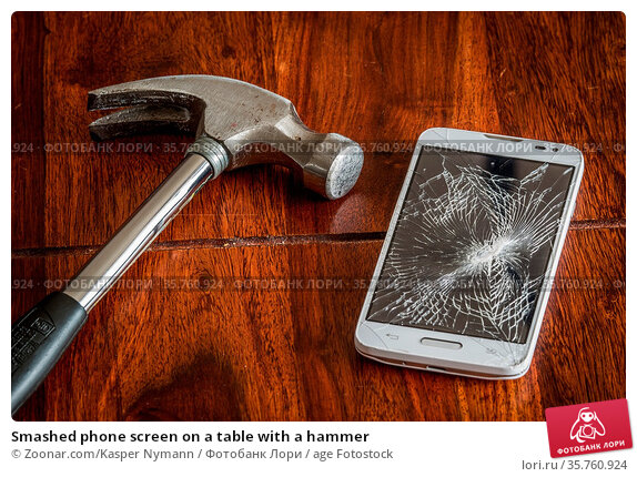 Smashed phone screen on a table with a hammer. Стоковое фото, фотограф Zoonar.com/Kasper Nymann / age Fotostock / Фотобанк Лори
