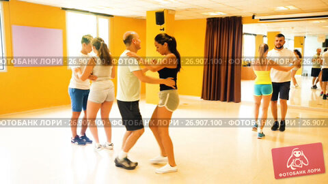 Купить «Smiling adults dancing bachata together in dance studio», видеоролик № 26907100, снято 6 июля 2017 г. (c) Яков Филимонов / Фотобанк Лори