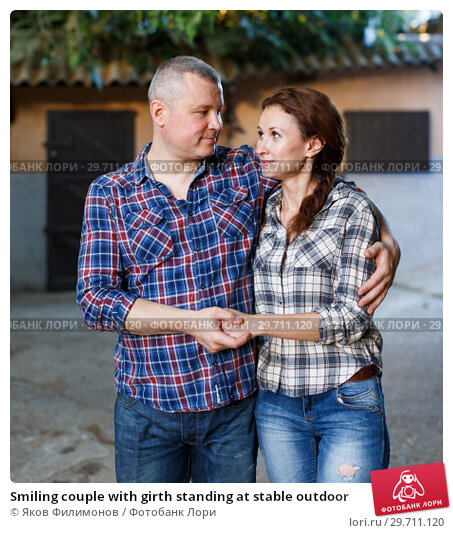 Купить «Smiling couple with girth standing at stable outdoor», фото № 29711120, снято 4 июля 2018 г. (c) Яков Филимонов / Фотобанк Лори