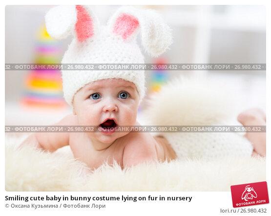 Купить «Smiling cute baby in bunny costume lying on fur in nursery», фото № 26980432, снято 7 октября 2015 г. (c) Оксана Кузьмина / Фотобанк Лори