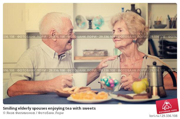 Купить «Smiling elderly spouses enjoying tea with sweets», фото № 29336108, снято 28 августа 2017 г. (c) Яков Филимонов / Фотобанк Лори