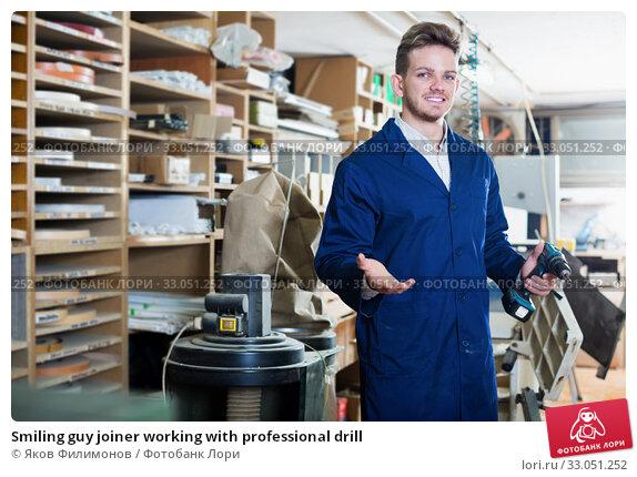 Купить «Smiling guy joiner working with professional drill», фото № 33051252, снято 7 ноября 2016 г. (c) Яков Филимонов / Фотобанк Лори