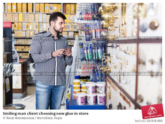 Smiling man client choosing new glue in store. Стоковое фото, фотограф Яков Филимонов / Фотобанк Лори