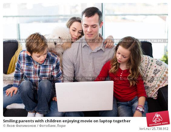 Купить «Smiling parents with children enjoying movie on laptop together», фото № 25738912, снято 23 декабря 2016 г. (c) Яков Филимонов / Фотобанк Лори