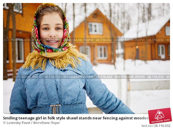 Купить «Smiling teenage girl in folk style shawl stands near fencing against wooden houses on winter day», фото № 28116032, снято 4 февраля 2017 г. (c) Losevsky Pavel / Фотобанк Лори