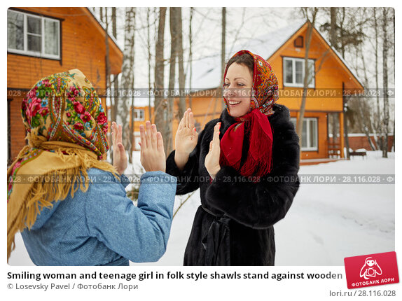 Купить «Smiling woman and teenage girl in folk style shawls stand against wooden houses and play okie-dokie on winter day», фото № 28116028, снято 4 февраля 2017 г. (c) Losevsky Pavel / Фотобанк Лори
