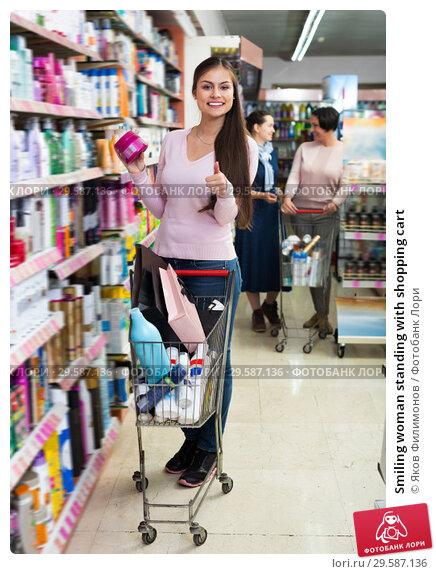 Купить «Smiling woman standing with shopping cart», фото № 29587136, снято 17 февраля 2019 г. (c) Яков Филимонов / Фотобанк Лори