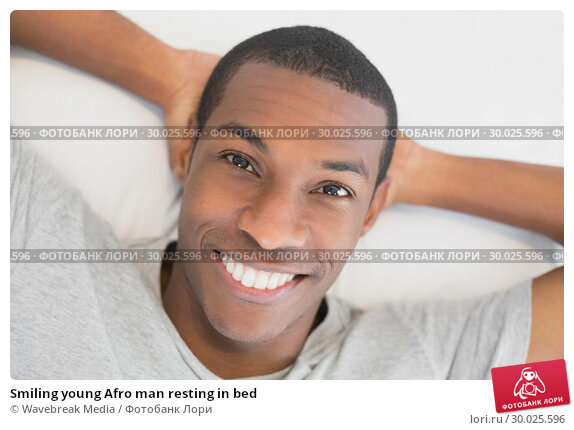 Купить «Smiling young Afro man resting in bed», фото № 30025596, снято 26 июля 2013 г. (c) Wavebreak Media / Фотобанк Лори