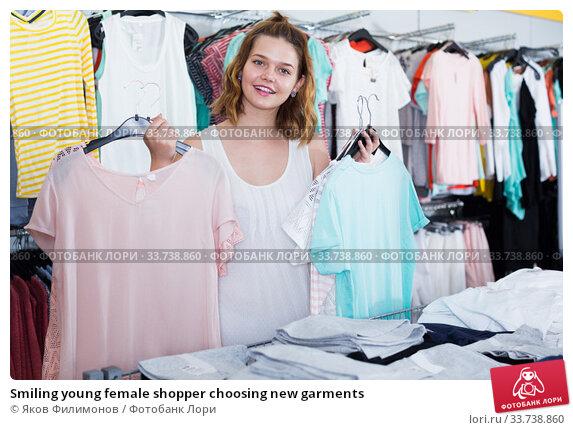 Купить «Smiling young female shopper choosing new garments», фото № 33738860, снято 19 июня 2017 г. (c) Яков Филимонов / Фотобанк Лори