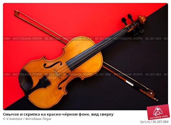 Купить «Смычок и скрипка на красно-чёрном фоне, вид сверху», фото № 30307084, снято 3 марта 2019 г. (c) V.Ivantsov / Фотобанк Лори