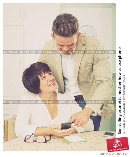 Купить «Son telling brunette mother how to use phone», фото № 29383332, снято 5 июля 2020 г. (c) Яков Филимонов / Фотобанк Лори