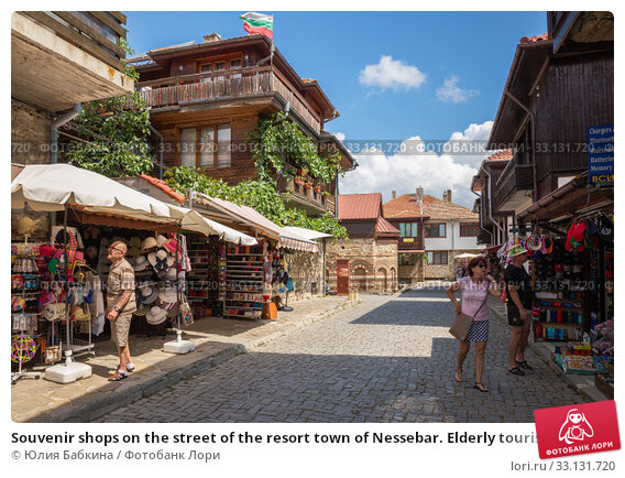 Souvenir shops on the street of the resort town of Nessebar. Elderly tourists look at souvenirs (2019 год). Редакционное фото, фотограф Юлия Бабкина / Фотобанк Лори