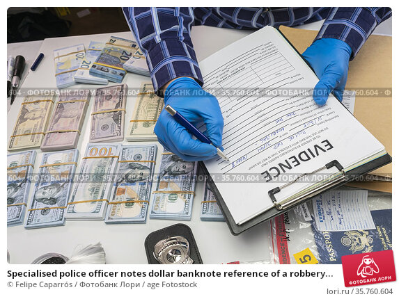 Specialised police officer notes dollar banknote reference of a robbery... Стоковое фото, фотограф Felipe Caparrós / age Fotostock / Фотобанк Лори