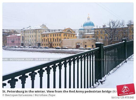 Купить «St. Petersburg in the winter. View from the Red Army pedestrian bridge (Krasnoarmeysky Bridge) across the Fontanka river to the blue domes of the Trinity Cathedral on a snowy day», фото № 29419640, снято 26 января 2016 г. (c) Виктория Катьянова / Фотобанк Лори