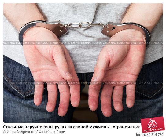 Купить «Стальные наручники на руках за спиной мужчины - ограничение свободы преступников при аресте или задержании полицией», фото № 2314760, снято 5 января 2011 г. (c) Илья Андриянов / Фотобанк Лори