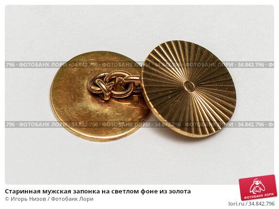 Старинная мужская запонка на светлом фоне из золота. Редакционное фото, фотограф Игорь Низов / Фотобанк Лори