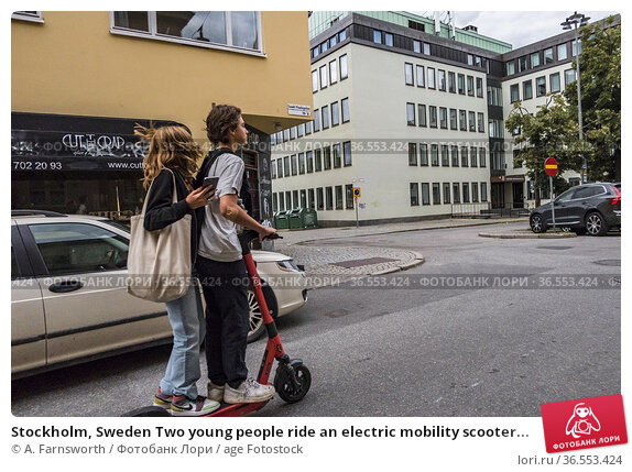 Stockholm, Sweden Two young people ride an electric mobility scooter... Редакционное фото, фотограф A. Farnsworth / age Fotostock / Фотобанк Лори