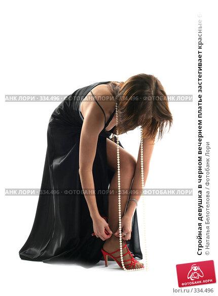 Стройная девушка в черном вечернем платье застегивает красные босоножки, фото № 334496, снято 31 мая 2008 г. (c) Наталья Белотелова / Фотобанк Лори