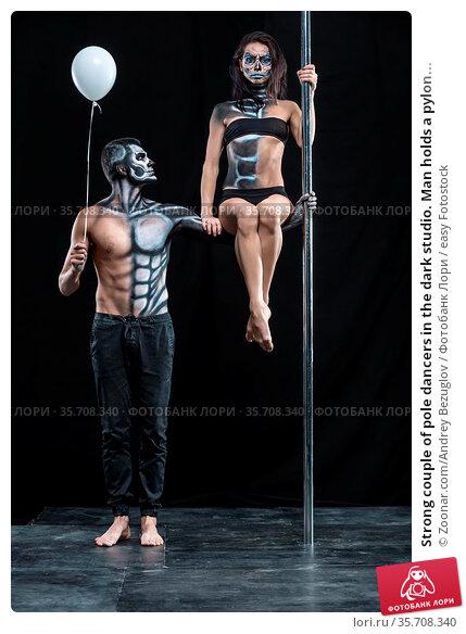 Strong couple of pole dancers in the dark studio. Man holds a pylon... Стоковое фото, фотограф Zoonar.com/Andrey Bezuglov / easy Fotostock / Фотобанк Лори