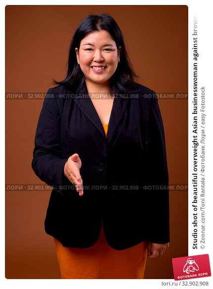 Studio shot of beautiful overweight Asian businesswoman against brown background. Стоковое фото, фотограф Zoonar.com/Toni Rantala / easy Fotostock / Фотобанк Лори