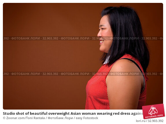 Studio shot of beautiful overweight Asian woman wearing red dress against brown background. Стоковое фото, фотограф Zoonar.com/Toni Rantala / easy Fotostock / Фотобанк Лори
