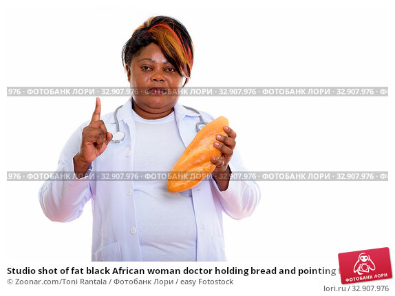 Studio shot of fat black African woman doctor holding bread and pointing finger up. Стоковое фото, фотограф Zoonar.com/Toni Rantala / easy Fotostock / Фотобанк Лори