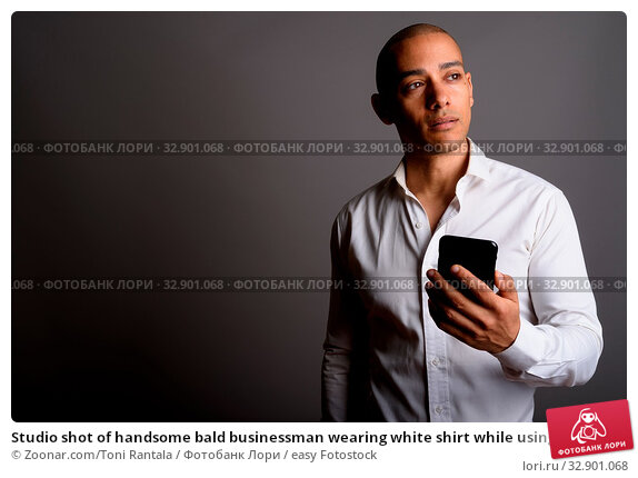Studio shot of handsome bald businessman wearing white shirt while using mobile phone against gray background. Стоковое фото, фотограф Zoonar.com/Toni Rantala / easy Fotostock / Фотобанк Лори