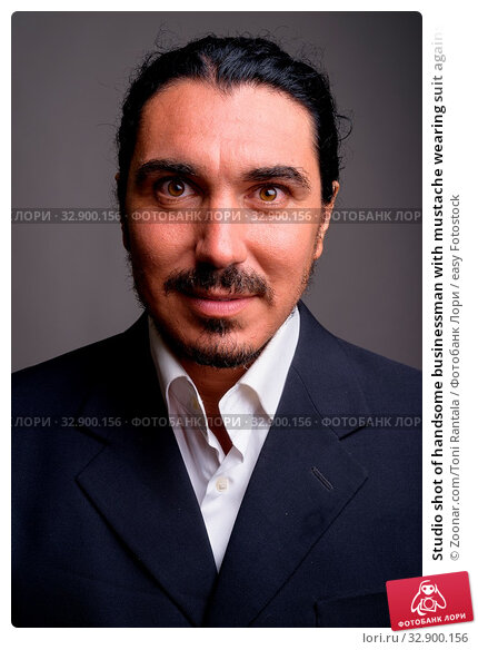 Studio shot of handsome businessman with mustache wearing suit against gray background. Стоковое фото, фотограф Zoonar.com/Toni Rantala / easy Fotostock / Фотобанк Лори