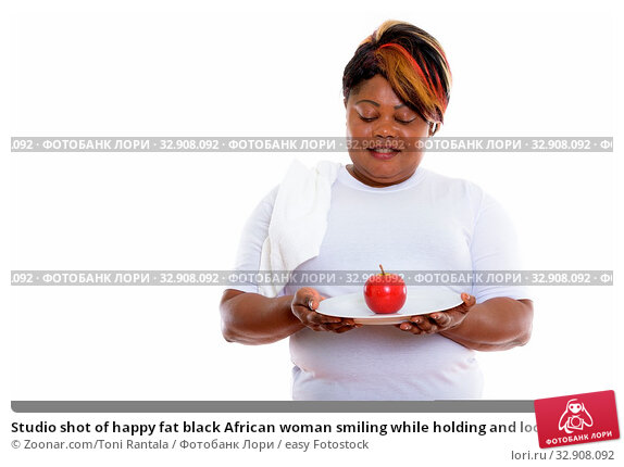 Studio shot of happy fat black African woman smiling while holding and looking at red apple served on white plate ready for gym. Стоковое фото, фотограф Zoonar.com/Toni Rantala / easy Fotostock / Фотобанк Лори