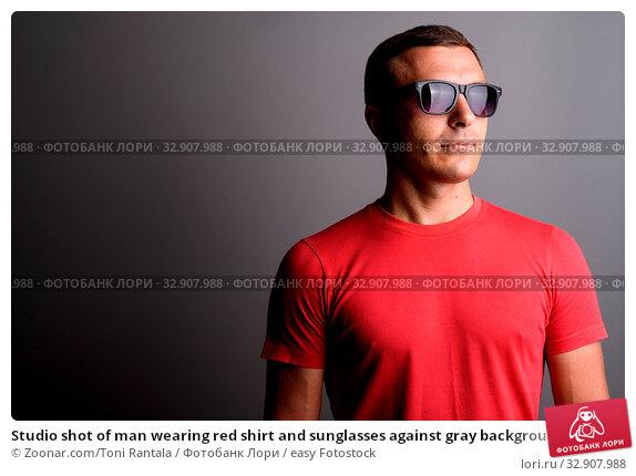 Studio shot of man wearing red shirt and sunglasses against gray background. Стоковое фото, фотограф Zoonar.com/Toni Rantala / easy Fotostock / Фотобанк Лори