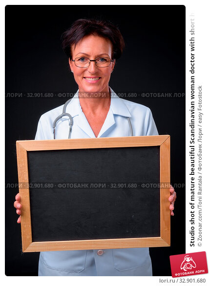 Studio shot of mature beautiful Scandinavian woman doctor with short hair against black background. Стоковое фото, фотограф Zoonar.com/Toni Rantala / easy Fotostock / Фотобанк Лори
