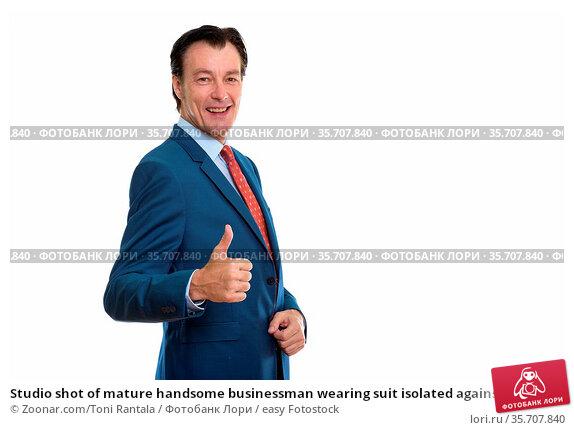 Studio shot of mature handsome businessman wearing suit isolated against... Стоковое фото, фотограф Zoonar.com/Toni Rantala / easy Fotostock / Фотобанк Лори