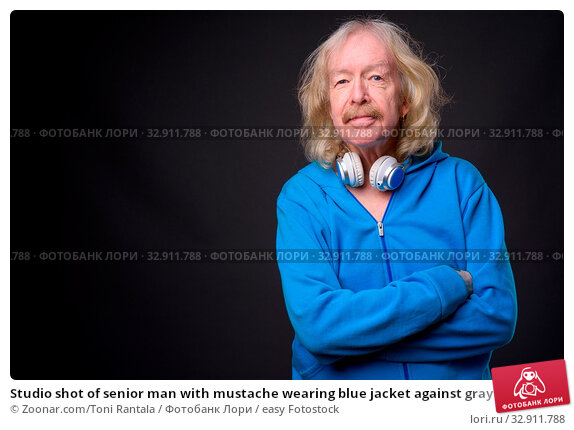 Studio shot of senior man with mustache wearing blue jacket against gray background. Стоковое фото, фотограф Zoonar.com/Toni Rantala / easy Fotostock / Фотобанк Лори